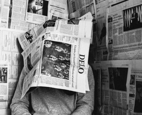 Man under newspapers