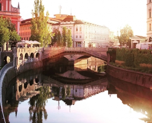 River in Slovenia, with sun reflecting in the water and old nice buildings on the sides
