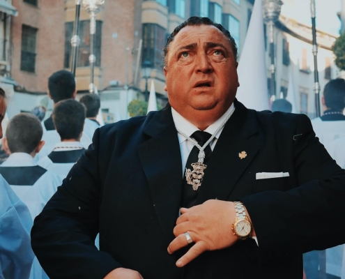 Man wearing an expensive black suit being shocked or suprised in a crowd of church choir children