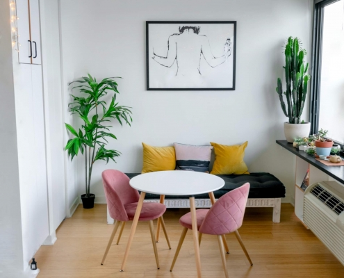 Airbnb room with a table and chairs around it and a cactus by thh window